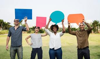 Four people of different ethnicity holding speech bubbles or callouts