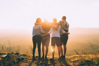 Four friends together, looking out towards a sunny vista